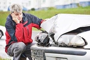 Man crouching next to crashed car